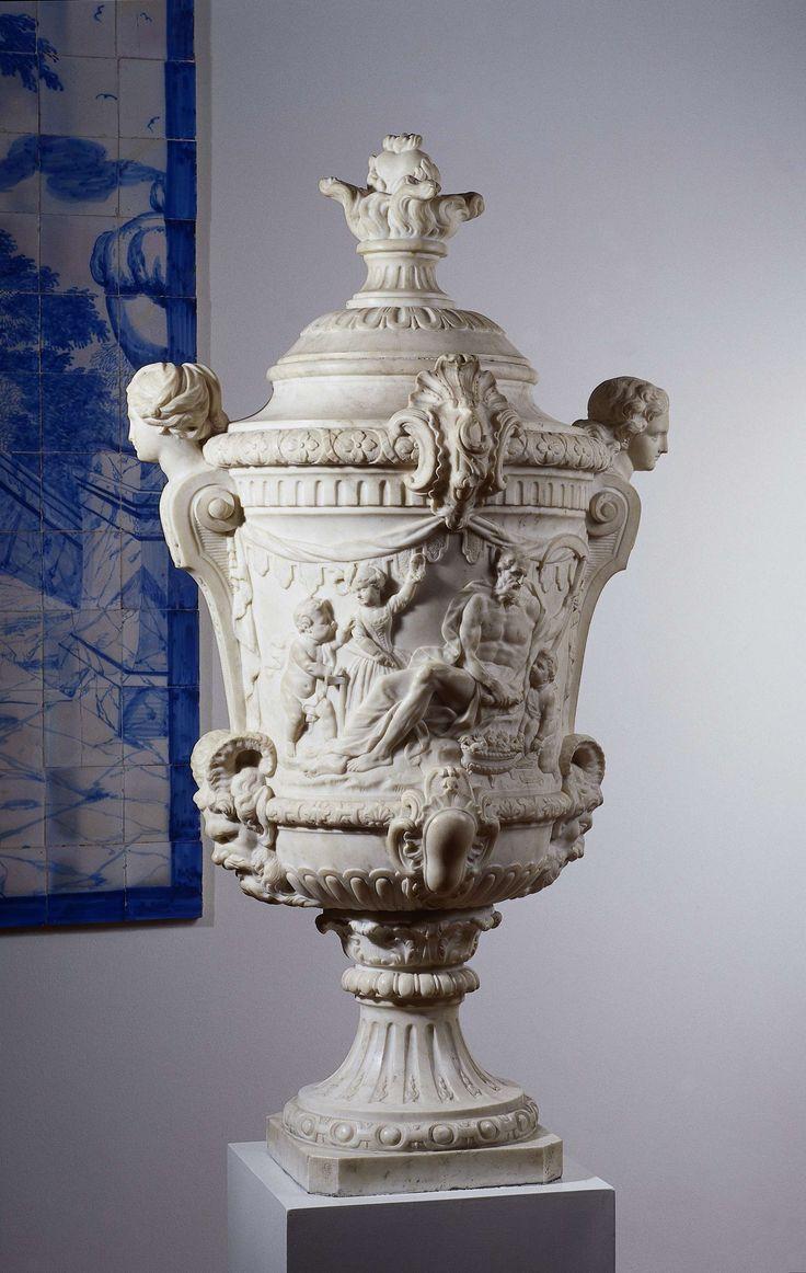 Jacobus Cressant | Two garden vases with the Four Seasons, Jacobus Cressant, 1714 | Flora zit frontaal en houdt met de rechterhand een nestje met vogels vast en slaat haar linkerarm om het rechts van haar staande knaapje, dat de vogeltjes voert. Zij heeft het hoofd gewend naar twee, links van haar, met elkaar pratende kinderen: een staande, gehelmde jongen met zijn linkerhand op de naast hem staande fasces en zijn rechter op de schouder van een meisje, dat naast de mand met bloemen zit…