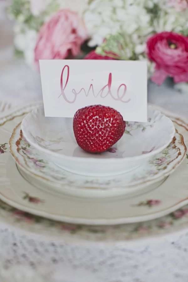 Strawberries holding escort cards for a strawberry shortcake inspired bridal shower.