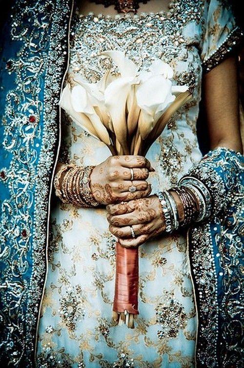 indian wedding saree. blue and white beaded lengha sari saree dress with lily bouquet and mehendi