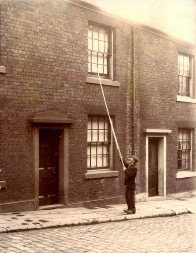 "A ""knocker-up"" waking up clients - the early 20th century version of alarm clocks."