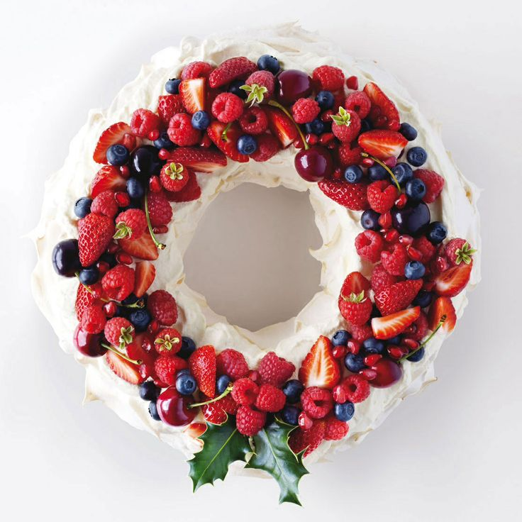 Pavlova decorated with fresh seasonal fruits, whipped cream and holly.  Oh how lucky I am too have a live holly bush on hand....