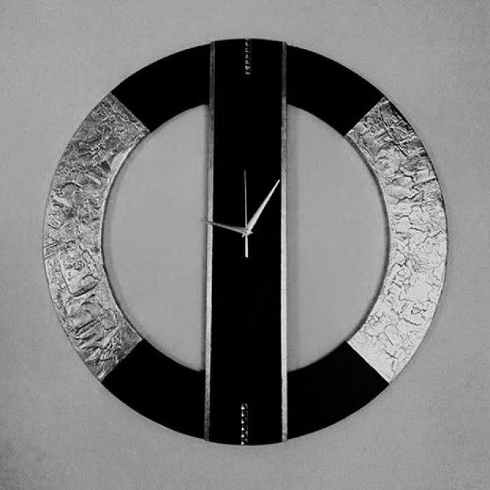 Χειροποίητο διακοσμητικό ρολόι τοίχου (minimal) φτιαγμένο με ακρυλικό μαύρο χρώμα και φύλλο ασημί. Πάστα διαμόρφωσης που δημιουργεί ανάγλυφη επιφάνεια στο εξωτερικό του κύκλου και διακριτικά κρύσταλλα swarovski με εντυπωσιακό design. Έχει περαστεί με βερνίκι σατινέ για την προστασία και όμορφο φινίρισμα. Oι δείκτες του ρολογιού είναι μεταλλικοί και ο μηχανισμός του αθόρυβος. Διαστάσειs: 60/60cm και 80/80cm