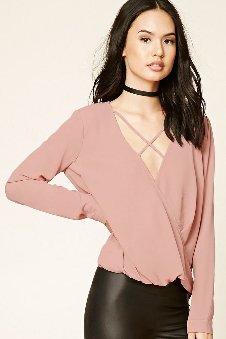 A textured woven shirt featuring a surplice front, strappy plunging neckline, long sleeves with button cuffs, and a curved back hem.
