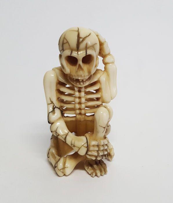 Ivoren netsuke van een zittend skelet gesigneerd - Japan - 1868-1912 (Meiji periode)  Prachtige Ivoren netsuke van een zittend skelet. Japans Meiji periode ( 1868-1912 ): hoogte 53 cm. Breedte 3cm. Gewicht 13 gram. De netsuke lijkt helemaal gaaf echter bij de ribben aan de achterkant zie ik wat vuil en/of restjes van wat lijm ? Dit is echter moeilijk te zien. Oordeel zelf aan de hand van alle foto's deze zijn onderdeel van de beschrijving. Voor verdere vragen altijd even mailen.Verzending…