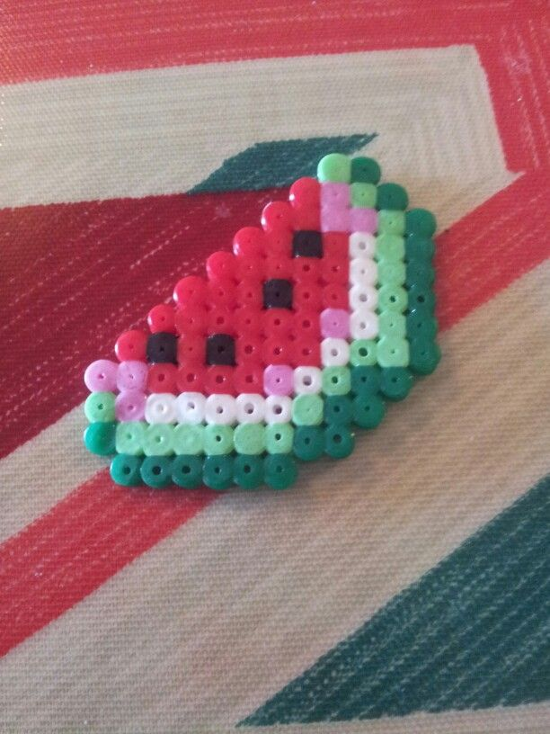 A slice of melon from Minecraft made out of red, pink, black , white, light green and dark black hama beads.