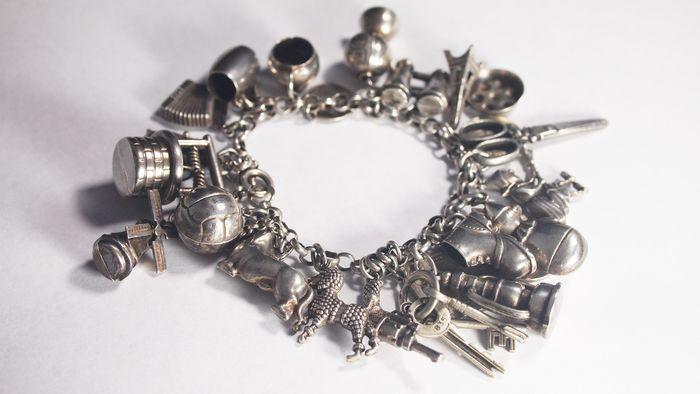 Bedelarmband met 24 bedels/ miniaturen, Amsterdam, jaren 50. De armband en de bedels zijn aangekocht bij een juwelier in de Van Limburg Stirumstraat te Amsterdam in de jaren 50.  Armband merkje: eikenblad + zwaardje Op de meeste bedels is een merkje terug te vinden: -pistool: 835 -poedel: 835 -teckel: geen merk  -voetbal: 835 -koekenpan: OEA + zwaardje 835 -wereldbol: zwaardje 835 -pot: waardje 835 -bierpul: merk niet te vinden, deksel is niet meer aanwezig -eiffeltoren: 835 -heks: zwaardje…