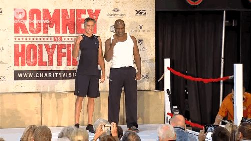 Mitt Romney and Evander Holyfield sizing each other up and having a laugh at the official weigh-in for their boxing match for charity tonight. Yup, Mitt Romney the politician is facing off against...