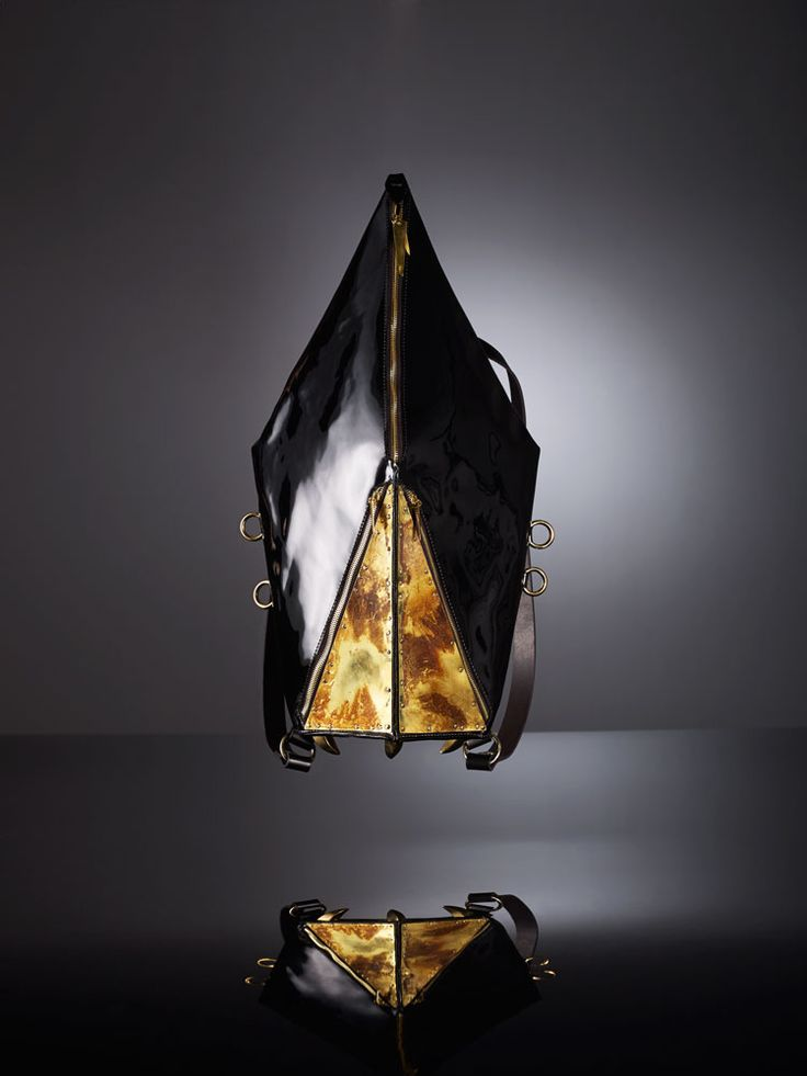 MRS HERSKIN HANDCRAFTED BACKPACK IN BLACK PATENT LEATHER  This unusual bag is handcrafted from black patent leather (calf).  Fastens with gold colored metal zip at front. Two zipped front pockets.  Finished with fire burnt polished brass hardware and handmade claw-shaped brass rivets on bott...