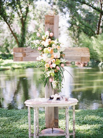 Flower adorned cross makes a breath taking alter! View More: http://marciemeredith.pass.us/kmweddingvendors