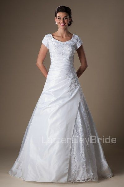 The Glenwood | This A-line silhouette gown has a sweetheart neckline with beaded applique overlay on the bodice and skirt with a beautiful and slimming wrap style waist.    Recommended Petticoat: A-line 2    Gown available in Ivory or White.    *Gown pictured in White.     Available at LatterDayBride.com or in Store Located in Salt Lake City, Utah