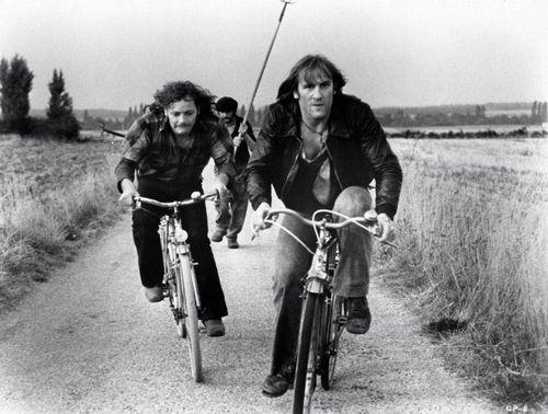 Patrick Dewaere and Gerard Depardieu ride bikes.