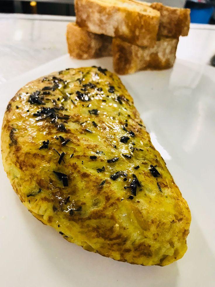 Tortilla de patata y trufa acompañada de pan de cristal