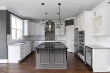 White kitchen with gray island. White and black granite counter tops. Prep sink. Gas range with mini mosaic tile. Wine refrigerator and wine rack.