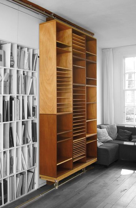 """""""A Sliding Bookcase Wall..."""" -- I have seen this attributed both to Erik Cox (at the click-through) and to Nico Sevenhuysen, both from The Netherlands, but I haven't been able to track down an original photo to prove or disprove either attribution. Whoever did it, I think I want to paint it white and add it to my house!"""