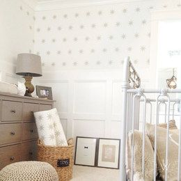 Eight point silver star wall decals in an equally spaced pattern placed on an off white wall behind a nursery crib and a wooden cabinet with a victorian style.