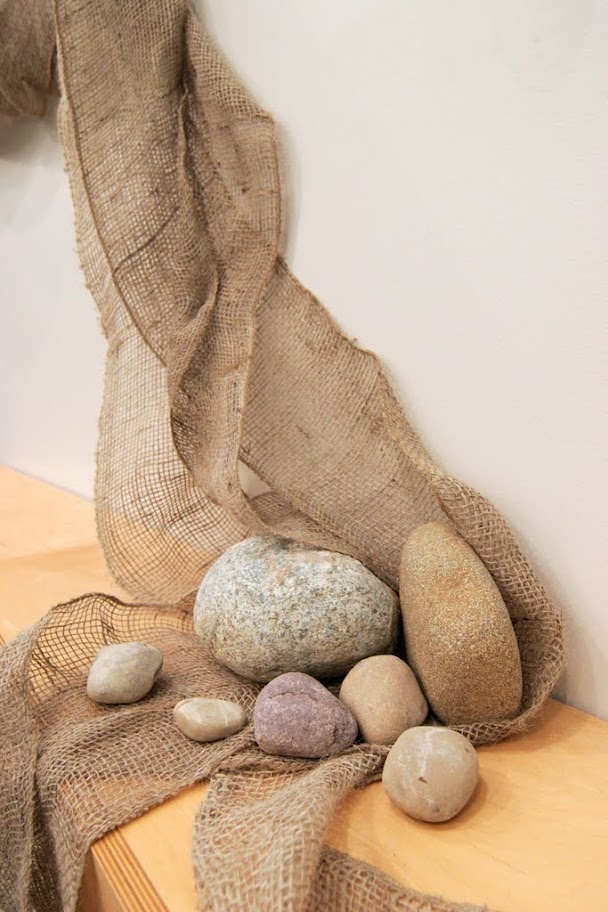 The horizontal band of burlap, that represents our humanity, terminates at the memorial table and is held in place by stones that represent the people of faith who have gone before.