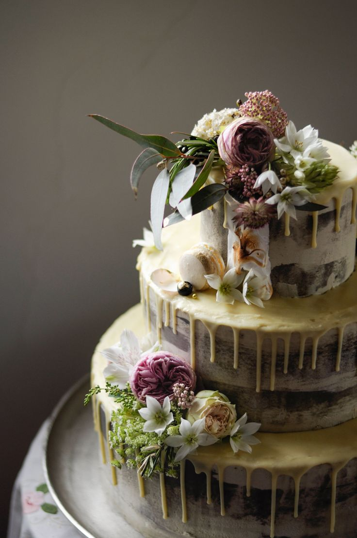 Three tiered Wedding cake by LionHeart. Rosemary Lemon Pound Cake, lemon curd filling, Rosemary buttercream, white chocolate drip, scorched Italian meringue and fresh floral finishes