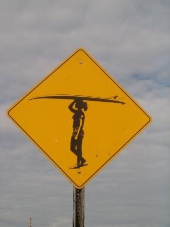 Surfer crossing road sign