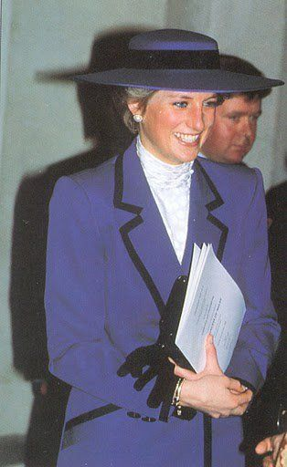 Princess Diana wore a purple blazer & pleated skirt by Catherine Walker & a Philip Somerville hat while visiting the crypt in St. Bride's Church in London December 1989.