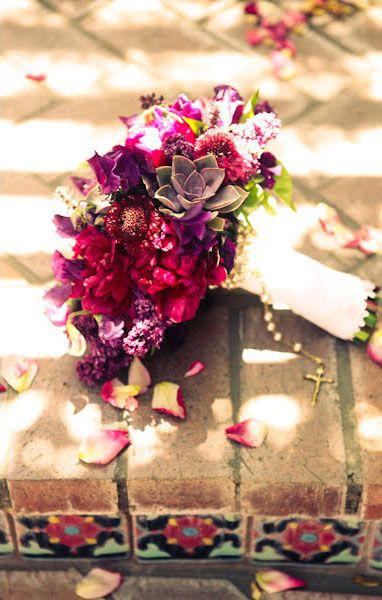 Bridal bouquet made up of purple lilac, fuschia peonies, raspberry toned scabiosa,