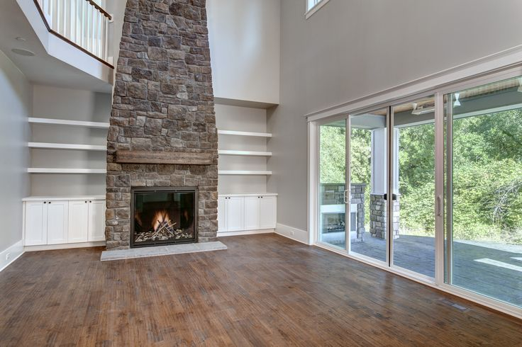 The stone fire place helps bring together the entire family room, along with the open sliding glass doors and spacious shelves. By American Classic homes