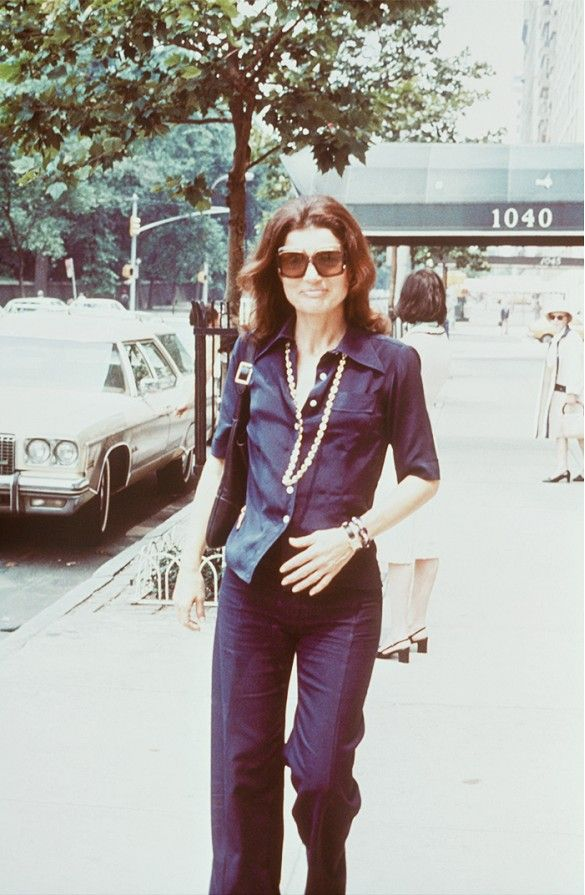 Jackie O wears a button-down blouse, gold chain necklace, stacked jewelry, pleated trousers, and square sunglasses