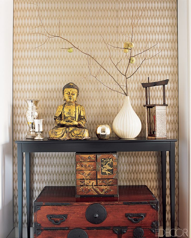 Lisa Pomerantz New York Apartment - Modern Home Design -  In a hallway, a small Chinese chest of drawers and a Japanese tansu are stacked beneath an ebonized Shaker-style console; the Buddah sculpture is iron, and the wall is covered in Jim Thompson'e Sprockets fabric.