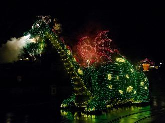 """A COLORFUL HOMECOMING - The Elliot dragon float from the classic 1977 Disney film """"Pete's Dragon"""" travels down the parade route at Disneyland park for the return of the Main Street Electrical Parade. The massive float decorated in thousands of twinkling green lights weighs 5,600 pounds, and measures 16 feet tall, 10 feet wide and 38 feet long.  The Main Street Electrical Parade will run for a limited-time, through June 18, 2017, at Disneyland park. (Scott Brinegar/Disneyland)"""