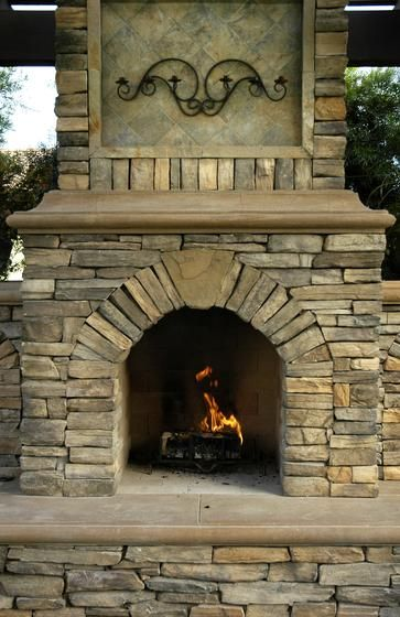 Rustic Outdoor Stone Fireplace With Wrought Iron Decor Above