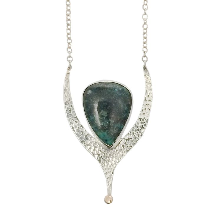 """This symbolic pendant is handmade in sterling silver and features a tear shaped chrysocolla stone and a contrasting brass detail. Hangs from a 24"""" sterling silver chain."""