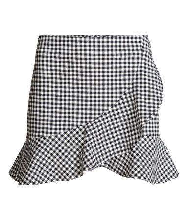 Schwarz/Weiß kariert. Kurzer Wickelrock aus stretchigem Baumwollstoff mit breitem Volant. Hinten ein sichtbarer Reißverschluss. Ungefüttert.