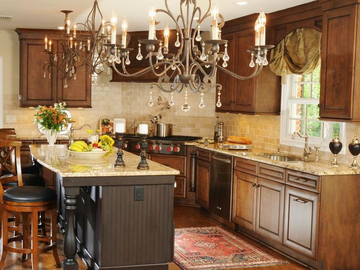 Ironwork chandeliers add a touch of grandeur to this traditional kitchen with wood-stained cabinets and a neutral subway tile backsplash.