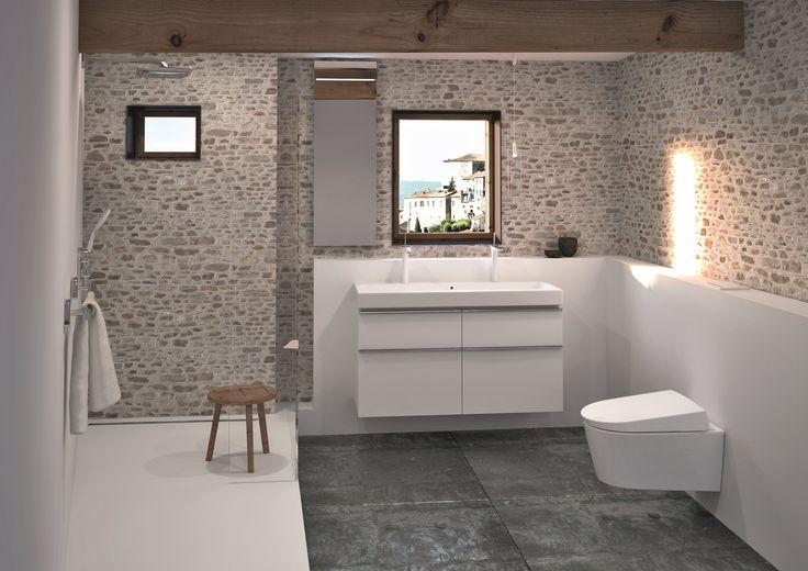 Cette salle de bains rustique vous donne une impression de vacances de premier ordre. Les couleurs claires sobres, les murs en pierre brute, et les poutres en bois créent un mélange de pureté et de cottage.
