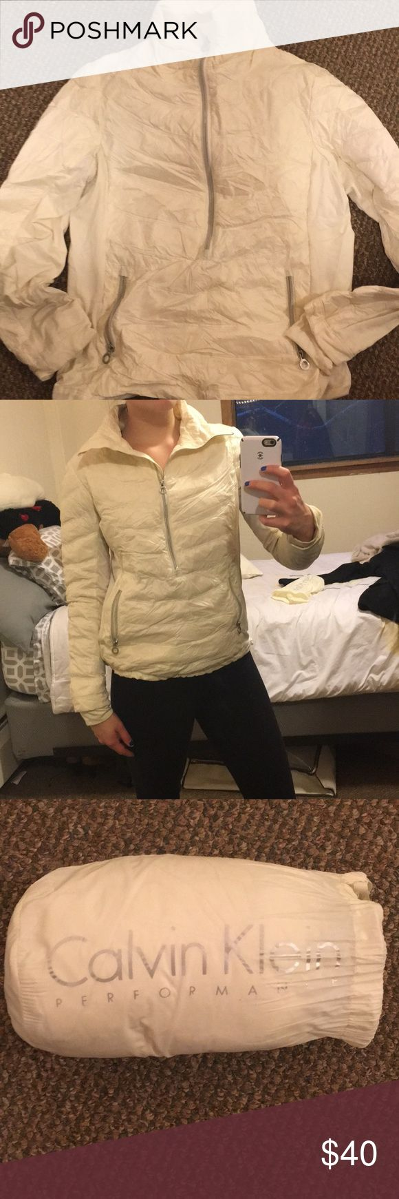 Calvin Klein Women's Pull-over Jacket. Calvin Klein cream colored light weight pull-over jacket. Comes with a cinch-able travel bag that the jacket rolls up into. Half-zip jacket with cinch-able waistline and two front pockets. Worn a few times but in great condition. Calvin Klein Jackets & Coats