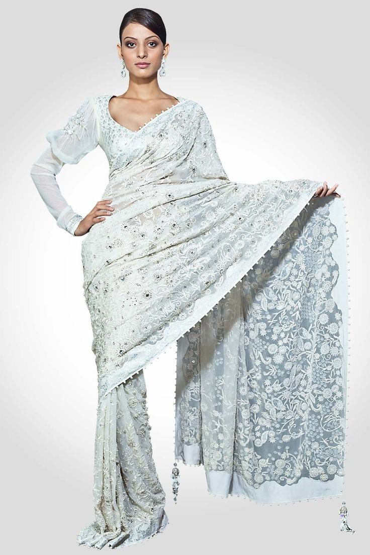 A white georgette saree rendered with  fine threadwork, stone pucker embroidery and elegant sparkles, worn with a brocade and net blouse with stone  pucker embroidery. A classy cocktail wear saree.