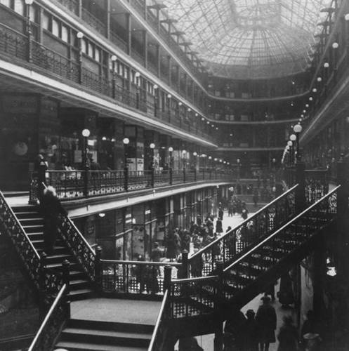 """""""Interior view of the main floor of the iron-and-glass enclosed Arcade, designed by John M. Eisenmann and George H. Smith, which opened in 1890.  The five-floor gallery connects two ten-story office buildings, one on Euclid Avenue and the other on Superior Avenue.  The Arcade today is a part of the Hyatt Hotel and still provides downtown workers with a place for lunch and shopping."""""""
