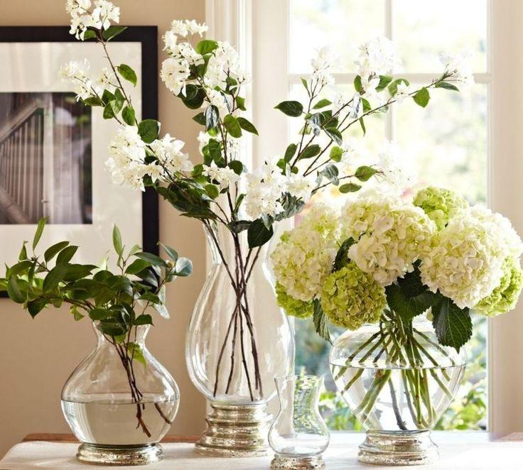 des hortensias et des branches à fleurs blanches sur la table