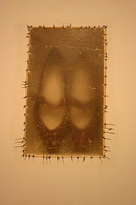 Doris Salcedo. The shoes which bear the marks of wear, all belonged to women who were 'disappeared', and were donated to the artist by victims' families. Their place here, hazily visible through the skin sheet, echoes the persistent memory for all those whose fate and whereabouts is unknown, permanently suspended between the present and the past.