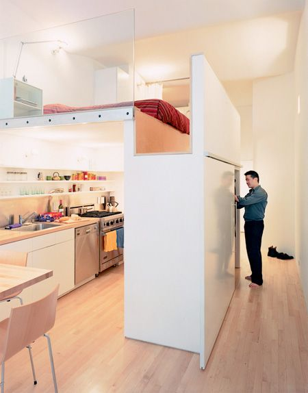 To maximize all usable space in this 700 square foot apartment, modern bedroom was constructed above the kitchen. Horizontal surfaces were covered with maple wood and vertical surfaces were painted white.