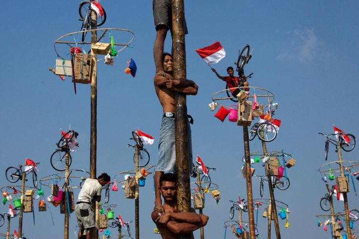 Indonesian men in teams of 4 try to climb to the top of a greased pole called a panjat pinang in order to get to the prizes tied to the top on August 17, 2015 in Jakarta, Indonesia. Cities and villages across Indonesia celebrated the country's 70th anniversary of Independence with traditional games, and music, and flag raising ceremonies.