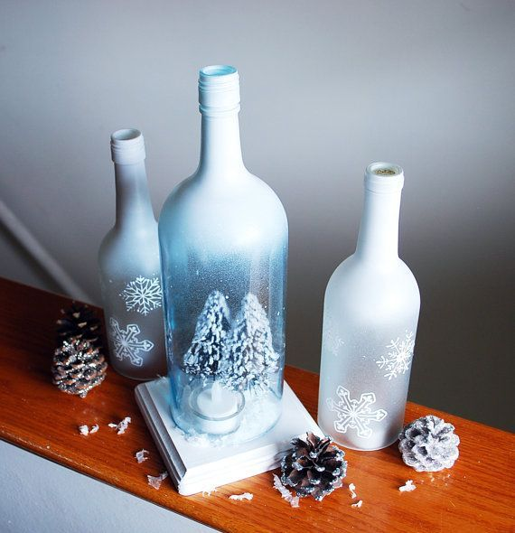 This is a set of hand frosted and painted wine bottles transformed into hurricane candle holders. The bottles have been hand cut and sanded to perfection so that there are no sharp edges. Tops of bottles are painted white and fade down into a frosted icy winter effect with white painted snowflakes. Largest bottle includes a little cozy winter scene with tea light candle holder as well as a hand painted wooden stand for the bottle to sit upon. This set is beautiful in the day time and just as…