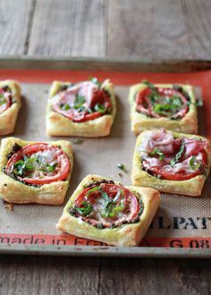 "Tomato Pesto Tarts  1 sheet  puff pastry, thawed  1/2 c of  pesto ,2  tomatoes, sliced 1/4 c shred Parm 5 - 6 fresh basil leaves, chiffonade oven 400, line  sheet w parchment  Cut pastry along the folds,cut into thirdsopposite way to create 9 squares.  Pesto: 2 t/square,  to 1/2"" from edges. One tomato slice in each. Sprinkle Parm over. Bake 12 mins. Sprinkle with fresh basil."