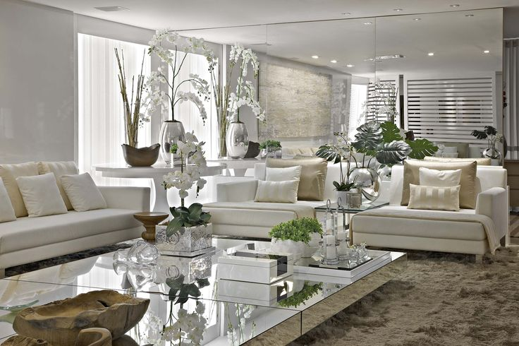 Espelhos, sem sombra de dúvidas, são grandes aliados na valorização da decoração de um ambiente. A mesa de centro também é revestida em espelho. Aliando o espelho + tons claros na decor temos como resultado um ambiente iluminando, requintado e amplo. Via Decora Líder.