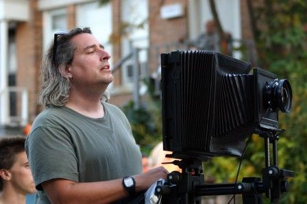 Photographer Gregory Crewdson shoots his still images as if he were Michelangelo Antonioni channeling Edward Hopper on a movie set. Since he shoots with a Hasselblad Sinar 8x10 camera, his field of composition includes people, sky, cars, streets and buildings. In essence, the scale of his compositions matches the possibilities inherent in the 8x10 camera format.