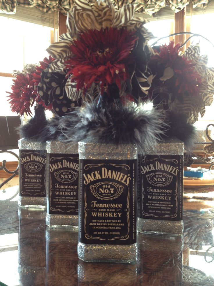 Jack Daniel's Centerpieces for birthday party!  A little glitter and floor pledge to coat the inside of the bottle then adorned with a little fluff wrist ring and flower picks - and TA DA!  Great recycled centerpieces!