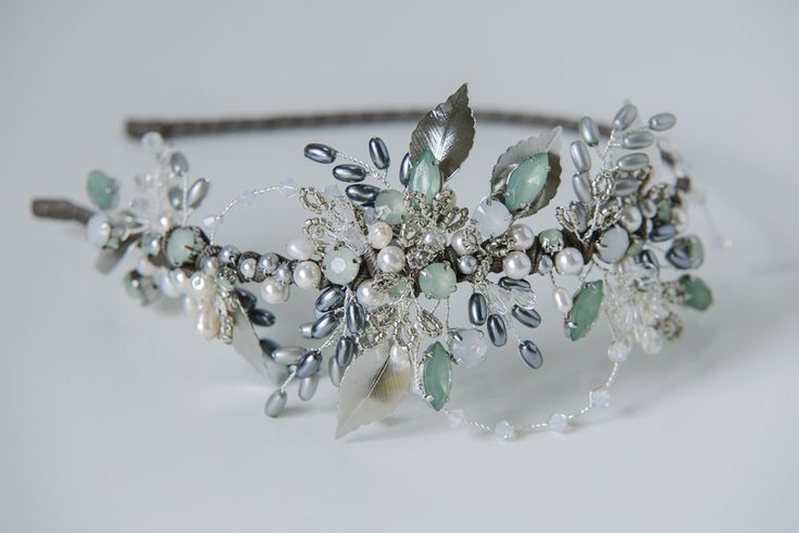 This is a one of a kind, statement headdress in antique silvers and greys with green crystal stones. I've used vintage Swarovski claw set crystals in a lovely, almost Georgian green colour as the focal part of this headdress. With silver coloured leaves and an abundance of Swarovski glass pearls in ivory, platinum and grey, rice shaped glass pearls and tiny Miyuki Delica glass seed beads in pewter to resemble leaves and ferns. Loops of Swarovski crystals in grey opal and branches of cle...
