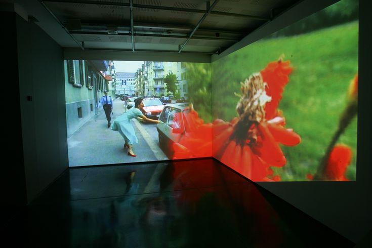 """Pipilotti Rist - """"Ever Is Over All"""" (1997) Due proiezioni a rallentatore sulle pareti adiacenti.  Il video di fiori rossi in un campo si armonizza con il video di una donna in scarpette rosse che passeggia. La fluidità di entrambe le scene è interrotta quando la donna violentemente fracassa una fila di parabrezza di auto con il fiore a stelo lungo. Video: https://www.youtube.com/watch?v=a56RPZ_cbdc"""