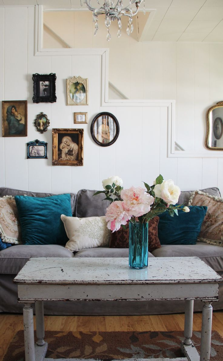 Love the rustic look, frames in different shapes, and pops of turqouise. And the flower arrangement on the table.