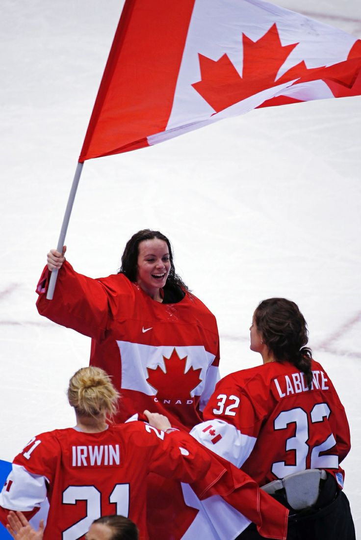 Goalkeeper Shannon Szabados of Canada (1) waves the Canadian flag after beating the U.S.A. 3-2 in overtime of the women's gold medal ice hockey game at the 2014 Winter Olympics in Sochi, Russia, Thursday, Feb. 20, 2014. (AP / Julio Cortez)