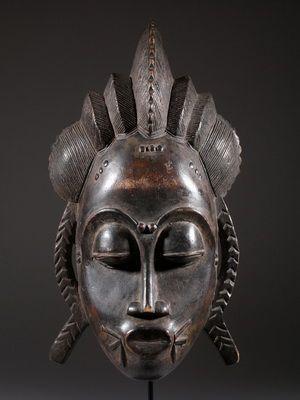 Masque africain Baoule - masques Kplé-kplé: le visage fait référence au soleil, et ses rayons sont représentés par des triangles peints. Les cornes de buffle sont un symbole de la fertilité. Ces masques sont employés dans les rites relatifs à l'agriculture, la fertilité et aussi dans les cérémonies funèbres.